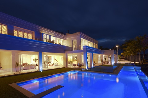 Rectangular in the ground pool at night with blue lighting